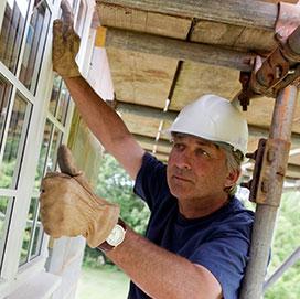 Construction worker installs window